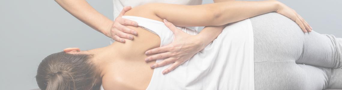 Practitioner stabilizing the shoulder of patient